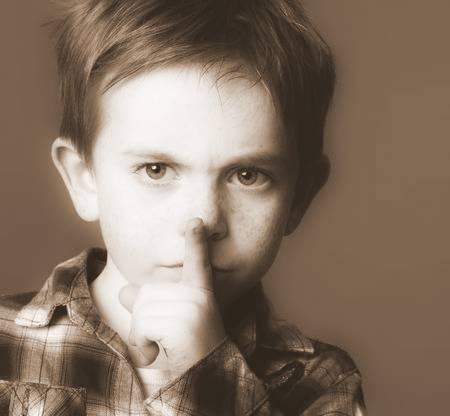 63663045-niño-de-6-años-seria-con-el-pelo-rojo-y-pecas-pidiendo-silencio-con-su-dedo-en-los-labios-con-el-ceño-fruncid.jpg